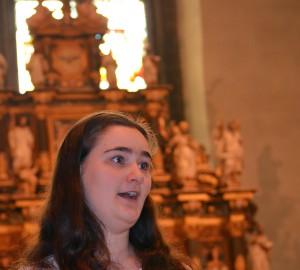 I förgrunden en sångerska. I bakgrunden en altartavla och ett stort ljust fönster.