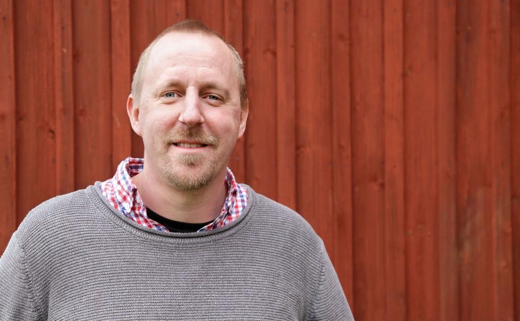 Nicklas Ekstrand i halvfigur framför en röd trävägg.