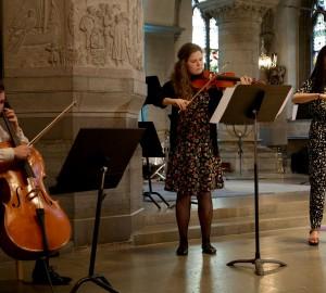 Tre klassiska musiker spelar stråkisntrument.