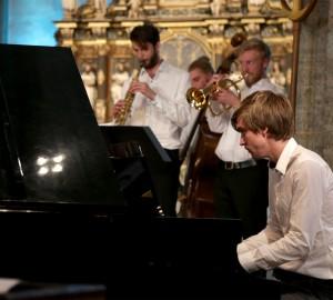 Pianist i förgrunden och delar av en jazzensemble i bakgrunden.