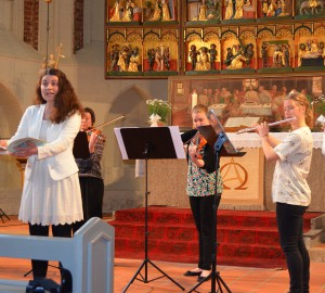 Deltagare sjunger och spelar stråkinstrument i en kyrka.