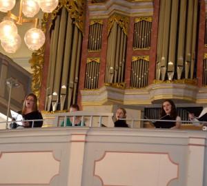 Sångare på en kyrkobalkong, framför en orgel.
