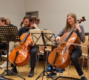 Två cellospelare i förgrunden.