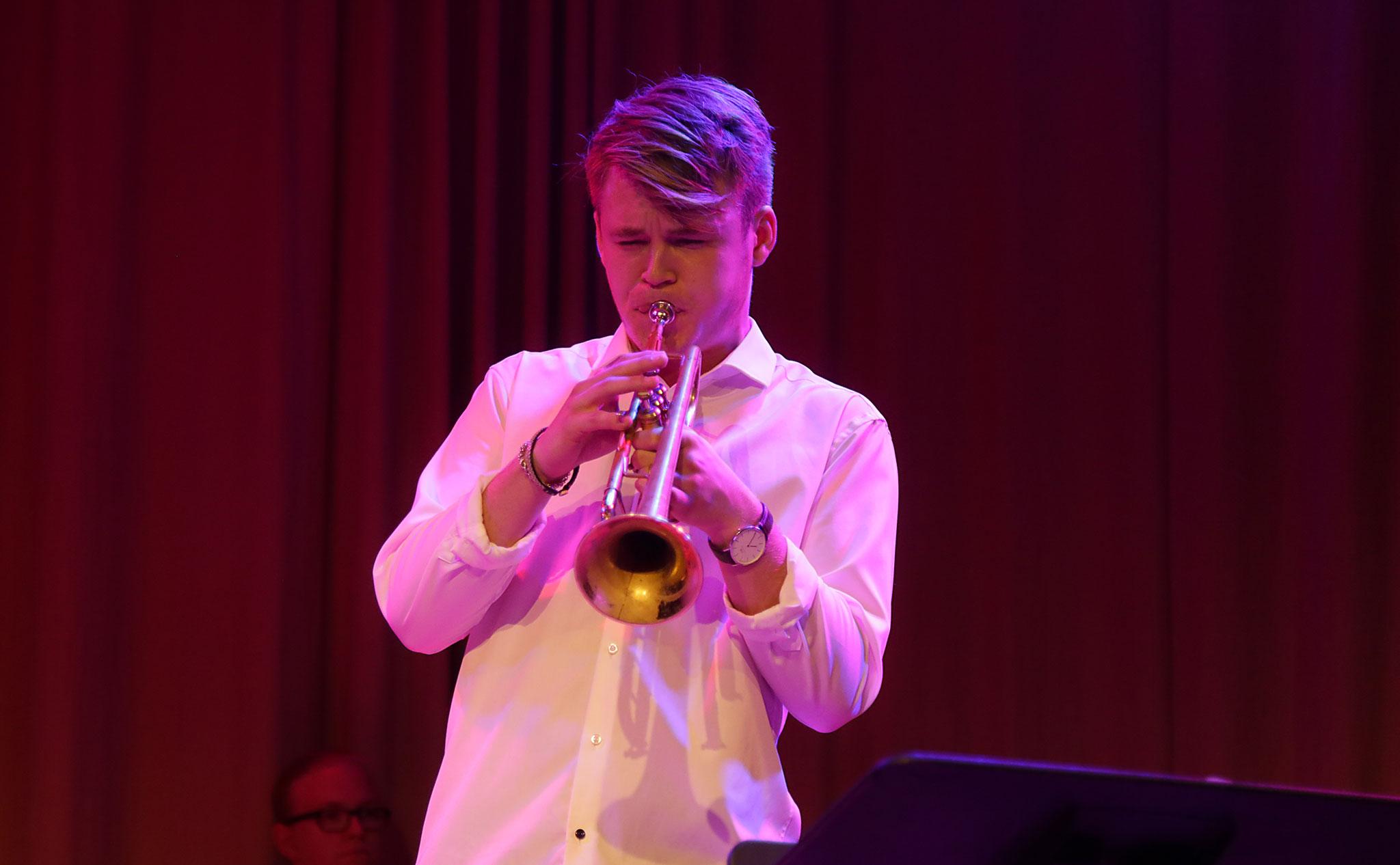 Trumpetare med vit skjorta, i lila scenljus.