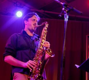 En saxofonist spelar solo, bakom huvudet lyser en stark scenlampa.