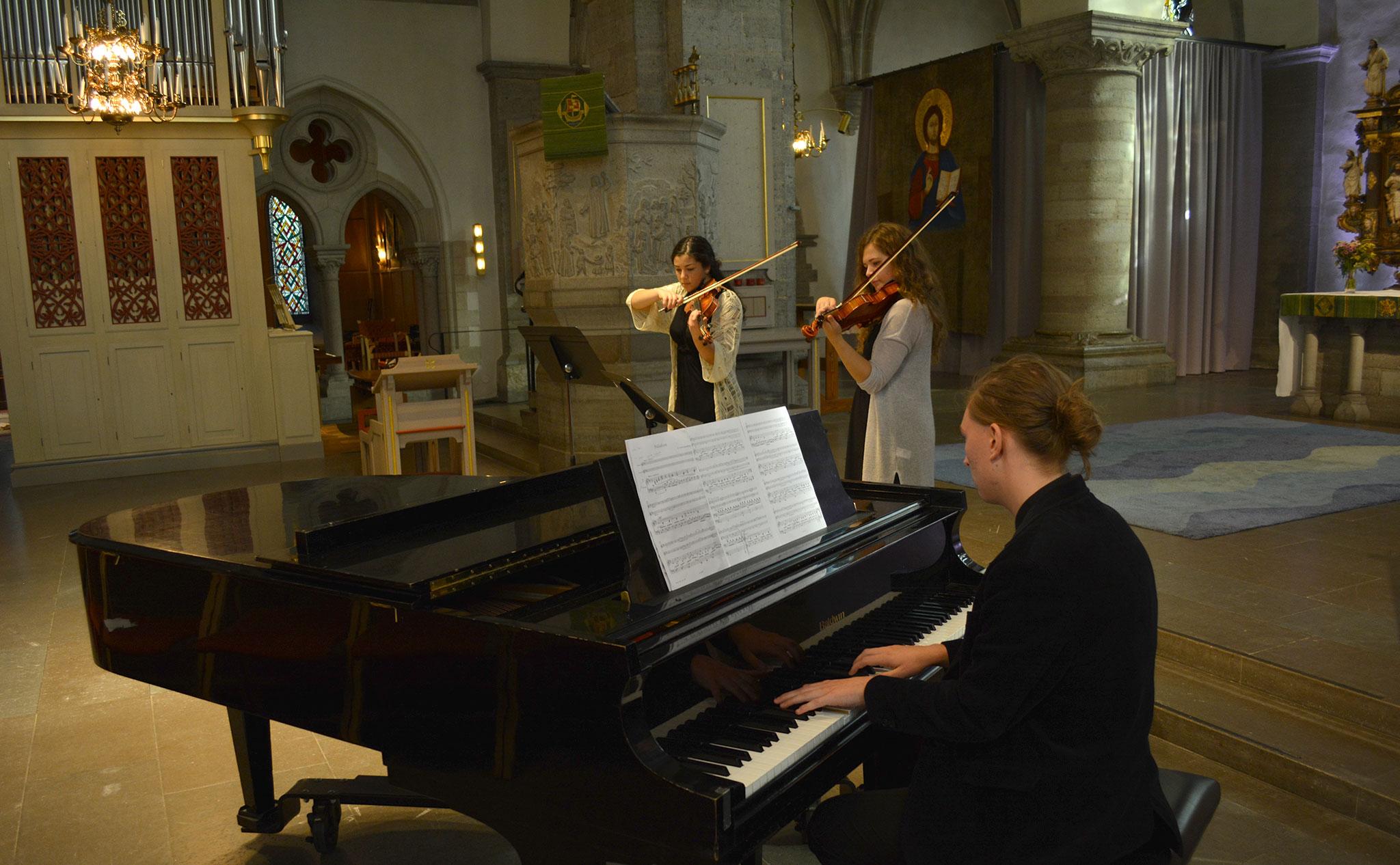 Konsert i kyrka. I förgrunden en pianist vid flyger. I bakgrunden blåsinstrument.