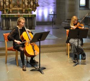 Två klassiska musiker i kyrkan, viola och fiol.