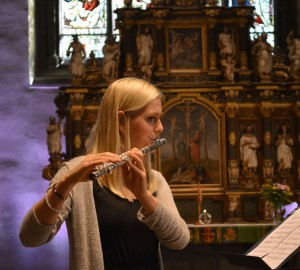 Flöjtspelare framför ett stort kyrkofönster.