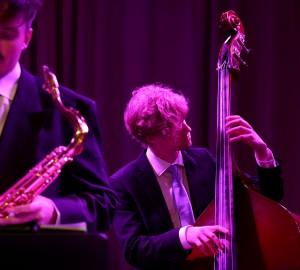 Jazzensemble, kontrabasist. I förgrunden ur fokus en saxofonist.