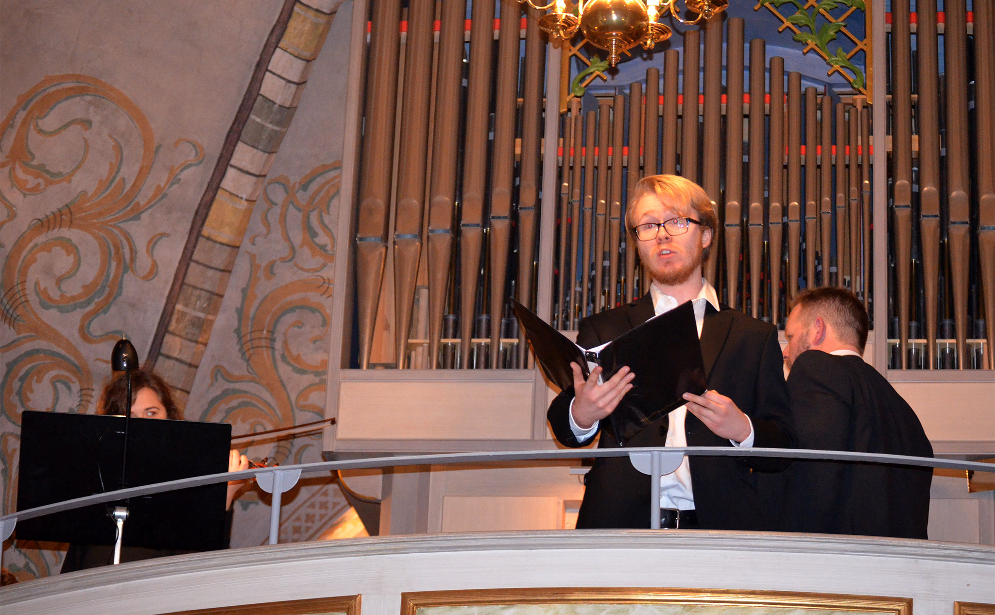Sångare på balkong i kyrka. Orgel i bakgrunden.