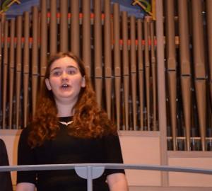 Sångerska på balkong i kyrka. Orgel i bakgrunden.