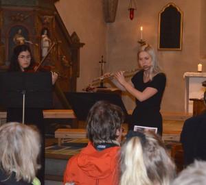 Två deltagare spelar flöjt respektive fiol framför publik i en kyrka.