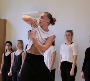 Dansare gör en rullande rörelse med händerna, nära kroppen.