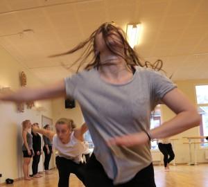 Dansare i förgrunden med huvudet bakåtkastat och håret för ansiktet.