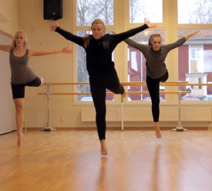Tre dansare mitt i ett hopp. Vända mot publiken, armarna utsträckta.