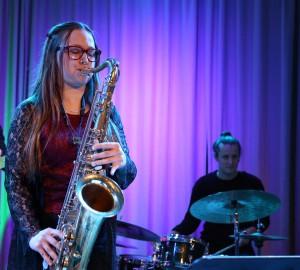Saxofonist i förgrunden, trummis och basist längre bak på scen.
