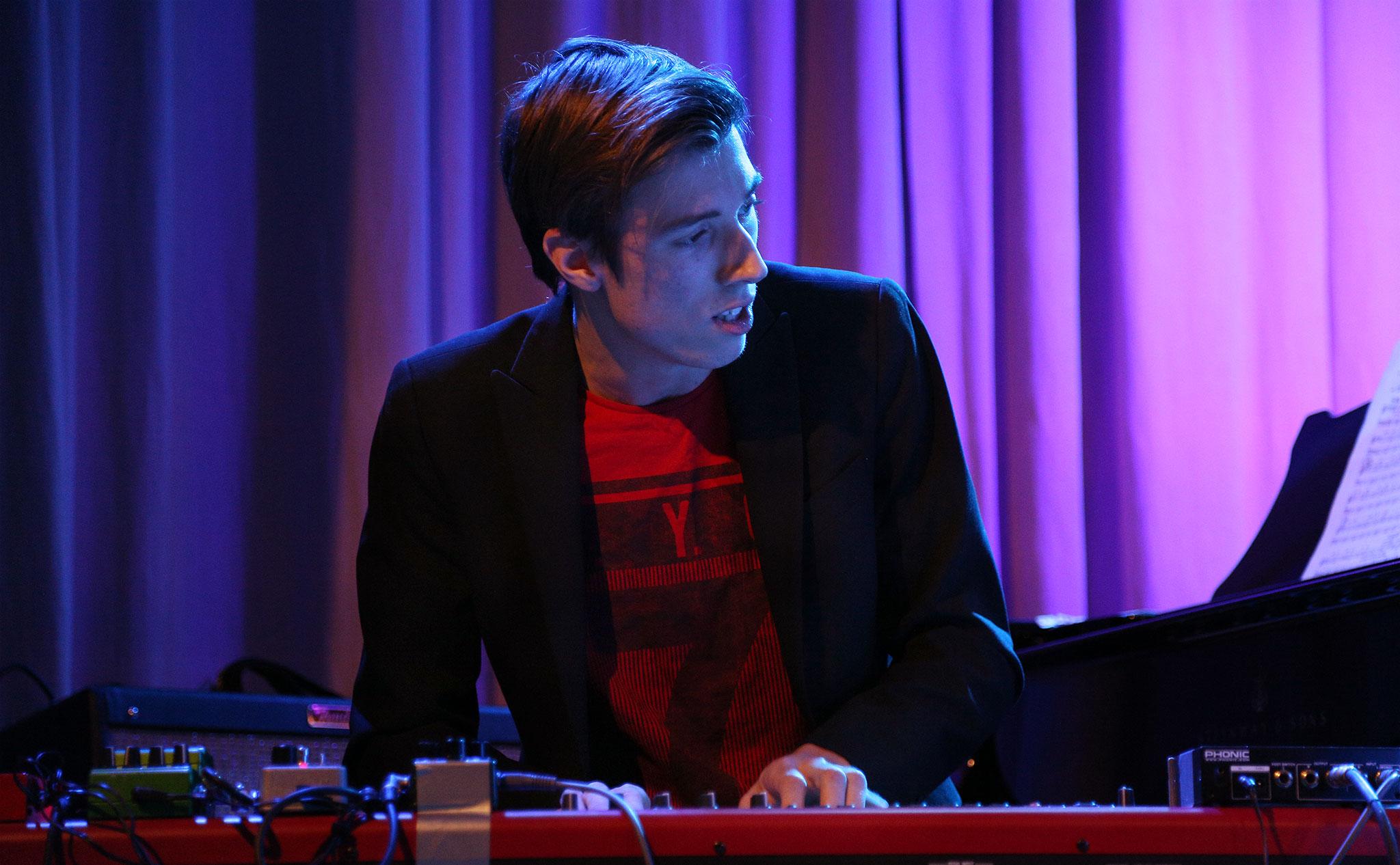 Deltagare spelar elpiano, framåtlutad och tittar åt höger i bild.
