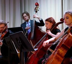 En del av en stråkorkester, fyra deltagare på fiol, basfiol och cello.