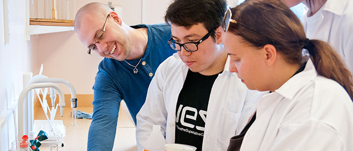 Laboration i naturvetenskapen. En lärare i blå tröja visar instruktioner för två deltagare i vita labbrockar.