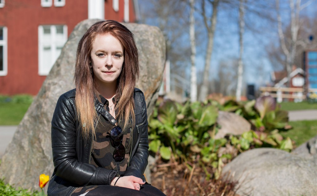 Porträttbild av Elin, som sitter framför en sten vid dammen på Kävesta folkhögskola. Elin har skinnjacka och långt hår.