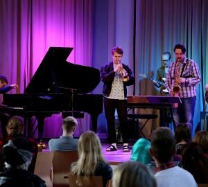Fem deltagare spelar jazz på scenen i Kävestas aula.
