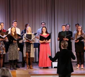 En fjorton personer stark kör står på aulans scen och sjunger. Nedanför scenen står en dirigent.
