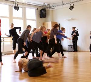 En grupp med dansare är samlad i mitten, i olika rörelser. Utanför gruppen rör sig tre andra dansare fort och suddigt. Bakom gruppen med dansare står ett band i svarta kläder.