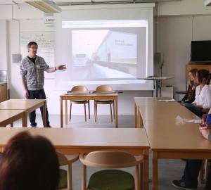 En lärare står framför en powerpointpresentation i ett klassrum. Runt ett U-format bord sitter flera deltagare och lyssnar.