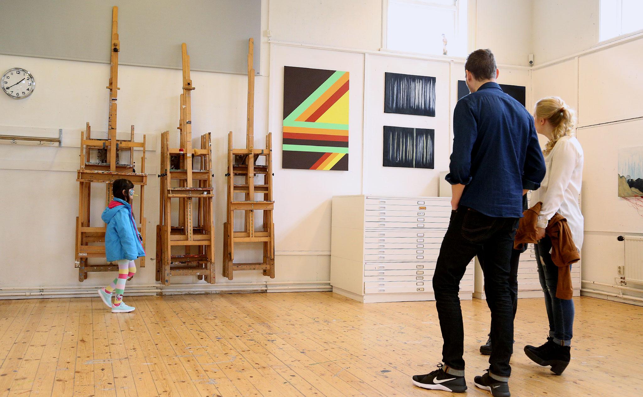 Tre personer står med ryggen mot kameran och titta på konsten som hänger på väggen: en tavla med geometriska mönster i klara färger och en tavla i svart och vitt, med abstrakt, skogsliknande motiv. Till vänster i bild går ett barn förbi med en klubba i munnen.