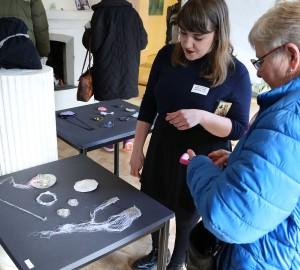 En yngre och en äldre kvinna står och tittar på ett bord med smycken och konstföremål.