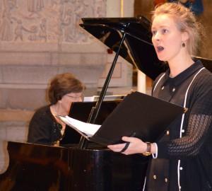 En deltagare sjunger, ackompanjerad av piano.