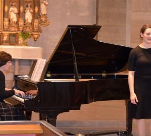En deltagare sjunger och en lärare ackompanjerar på piano.