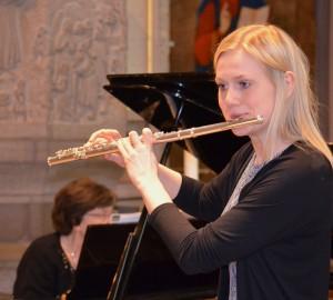 En deltagare spelar flöjt. I bakgrunden ackompanjerar en lärare på piano.