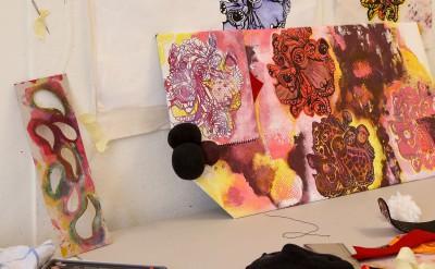 En tavla med färglatt tryck står på ett vitt arbetsbord.