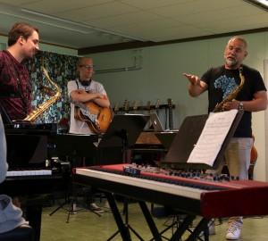 Fyra deltagare står runt Karl-Martin Almqvist som gestikulerar och förklarar en del av en låt.