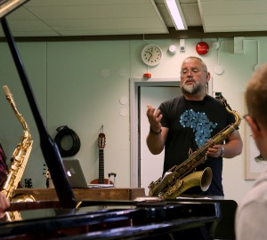 Karl-Martin Almqvist pratar med en saxofonist och en pianist under repetitionerna.
