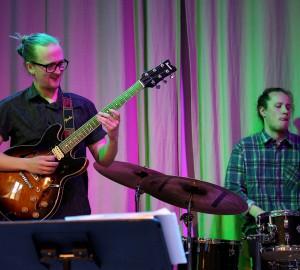 En deltagare spelar solo på gitarr, en annan kompar på trummor.