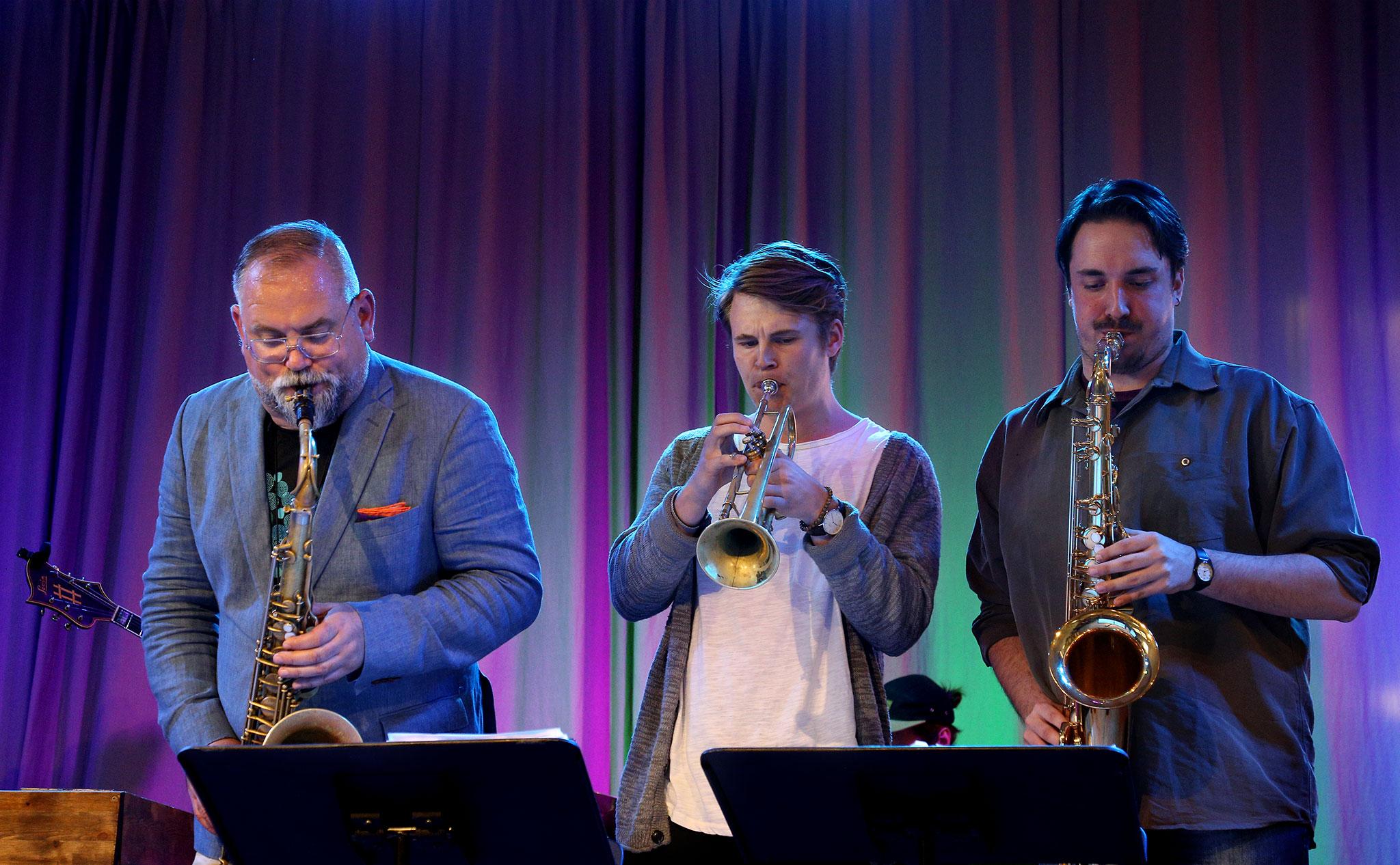 Karl-Martin Almqvist på saxofon tillsammans med ytterligare en saoxofonist och en trumpetare.