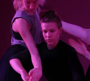Dansare i lila scenljus - en står bakom den andra. De når varandras händer.