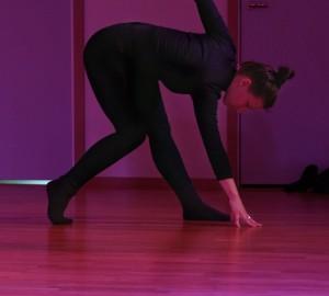 En dansare står framåtböjd i profil. En hand i golvet och en hand upp bakom ryggen, sträckt mot taket.