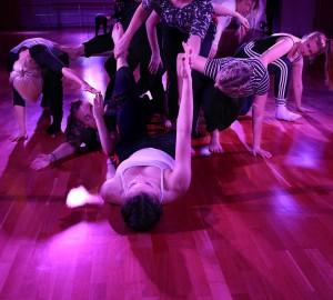 Dansare i lila scenljus. En mängd dansare bildar en formation där de ligger, står och lutar sig över och runt varandra.