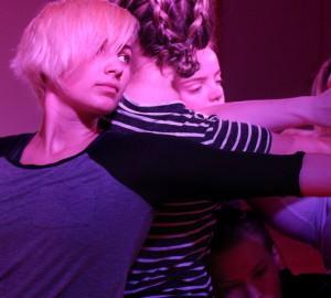 Två dansare med ryggarna mot varandra. Vi ser ansiktet på dansaren i förgrunden, som tittar ut åt höger i bilder.