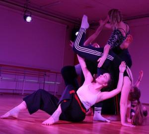En mindre grupp dansare fotade ur grodperspektiv. En sitter på golvet samtidigt som en annan böjer sig framstupa över den första, ner med händerna i golvet.