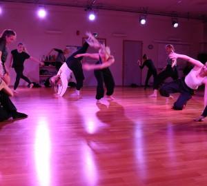 Dansare utspridda på scen i lila ljus. Många är suddiga av rörelse.