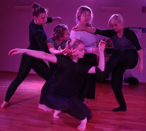 Fyra dansare står bakom en dansare som har hukat sig ner. Armar och ben korsas i ett virrvarr.