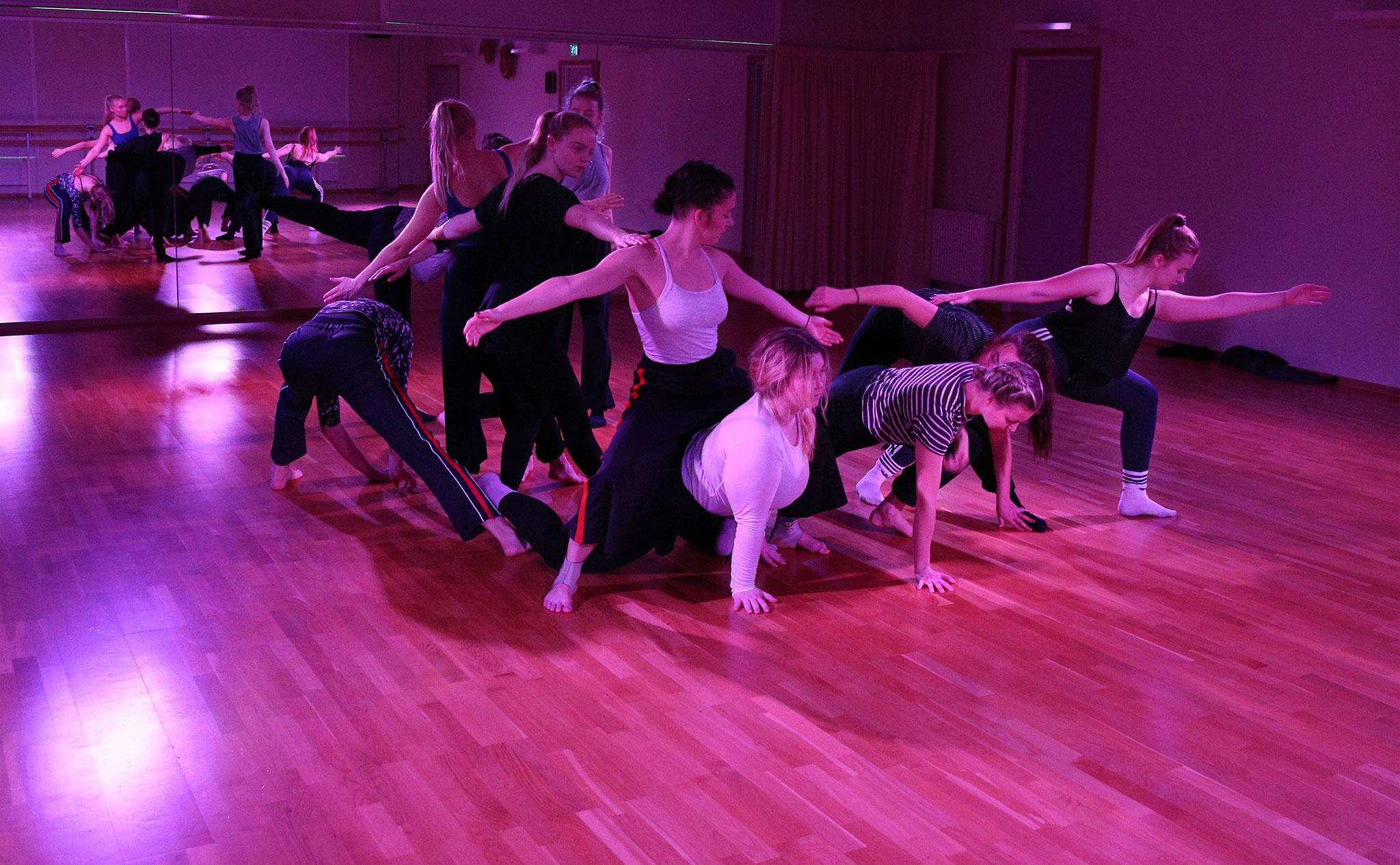 En grupp dansare sprider ut sig i en tät formation som ändå sträcker sig tvärs genom rummet.