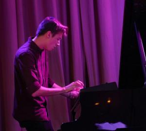 Pianist står upp vid flygel och spelar på elektroniskt klaviatur.