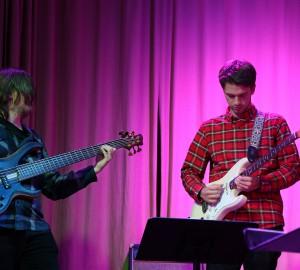Gitarrist spelar solo till höger. Bakom till vänster en basist.