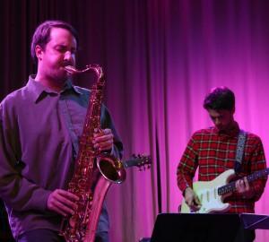Saxofonist mitt i solo till vänster. I bakgrunden till höger en gitarrist.