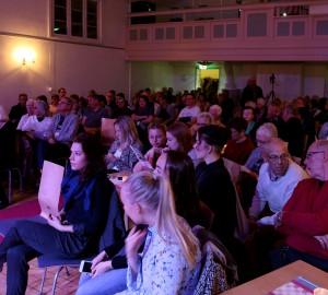Bild av publiken i Kävestas aula. Alla platser är fulla.